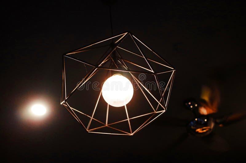 Lâmpada alaranjada preta do teto com a ampola fluorescente de poupança de energia imagem de stock
