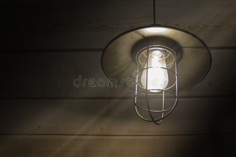 Lâmpada antiquado da lanterna do vintage que queima-se com uma luz macia do fulgor em um celeiro rústico antigo do país com a par fotografia de stock royalty free