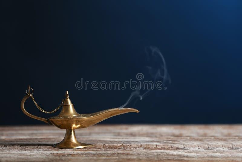 Lâmpada de Aladdin dos desejos na tabela de madeira imagens de stock