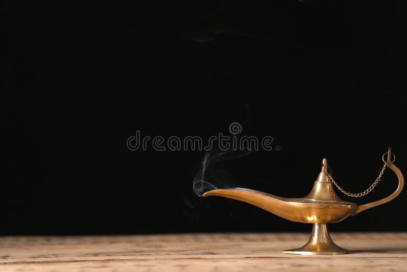 Lâmpada de Aladdin dos desejos na tabela de madeira fotografia de stock royalty free