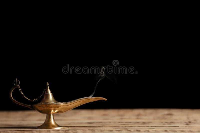 Lâmpada de Aladdin dos desejos na tabela de madeira foto de stock