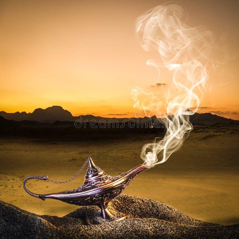 Lâmpada de aladim dourada clássica colocada na areia de uma duna com fumaça saindo fotografia de stock royalty free
