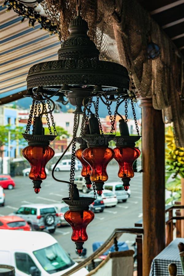 Lâmpada de bronze do vintage com as máscaras de vidro vermelhas que penduram sob um dossel Grupo de bananas maduras e uma vila lo foto de stock