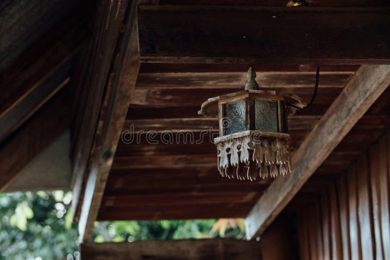 Lâmpada de madeira velha no terraço perto da casa fotografia de stock