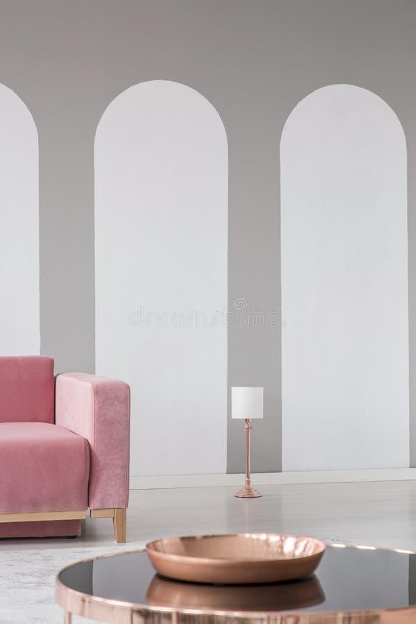 Lâmpada de mesa dourada de cobre por uma parede branca com arcos cinzentos em um interior à moda da sala de visitas com um sofá d fotos de stock royalty free