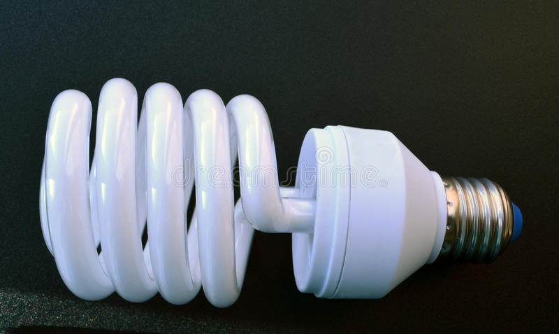 Lâmpada de poupança de energia no fundo cinzento foto de stock royalty free