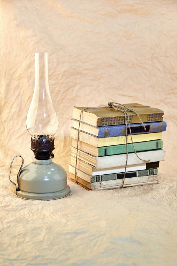 Lâmpada de querosene e pilha de livros velhos amarrados acima com corda fotos de stock royalty free