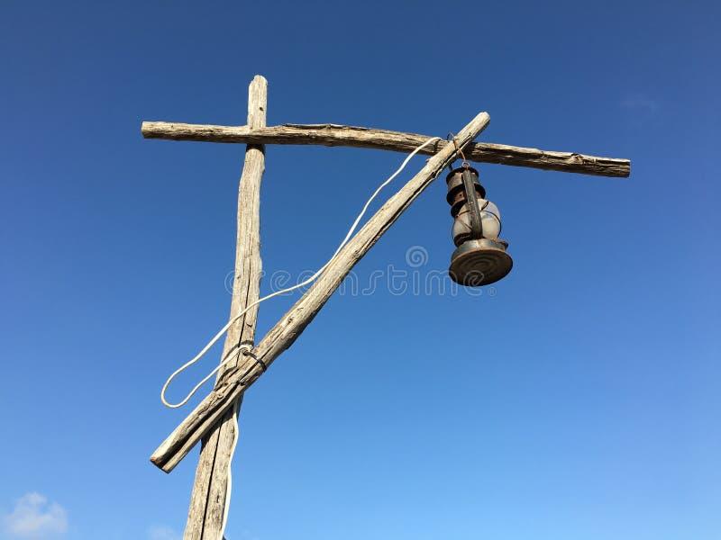 Lâmpada de querosene oxidada velha com um fio branco em um guindaste de madeira do cargo da rua imagens de stock royalty free
