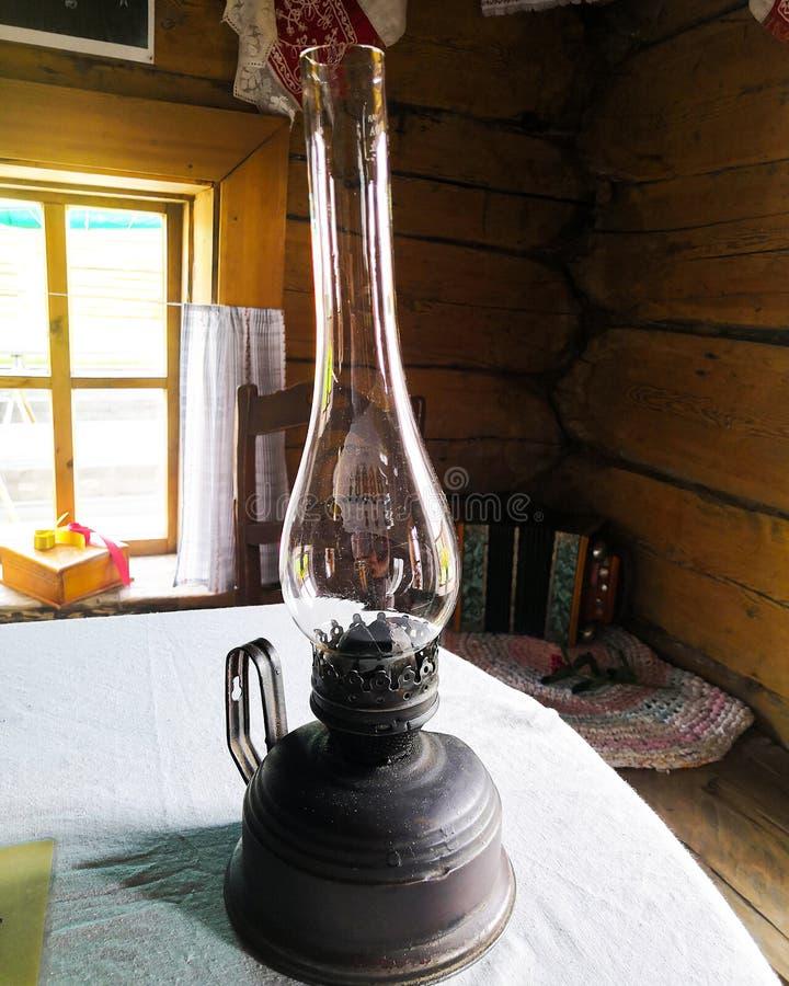 A lâmpada de querosene velha está na tabela Ainda vida com a lâmpada de querosene antiga empoeirada foto de stock royalty free