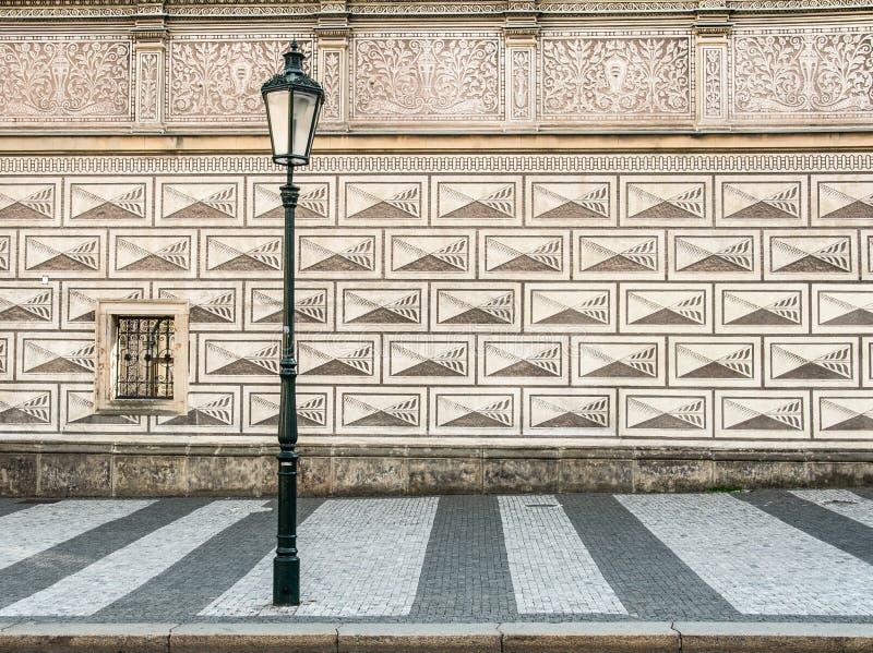 Lâmpada de rua antiga na frente de uma parede modelada maravilhosa da casa em Praga - República Checa fotografia de stock royalty free