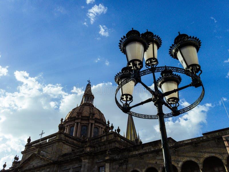 Lâmpada de rua, catedral, céu e nuvens no por do sol imagens de stock