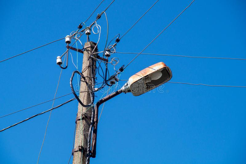 Lâmpada de rua com fios contra o céu azul imagem de stock