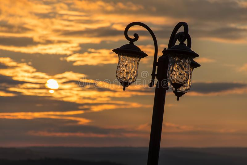 Lâmpada de rua contra o ajuste do sol nas nuvens em matiz douradas imagens de stock royalty free
