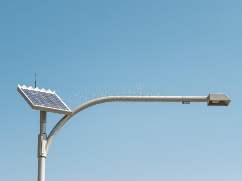 Lâmpada de rua da célula solar com o braço longo que está contra o dia do céu azul imagens de stock