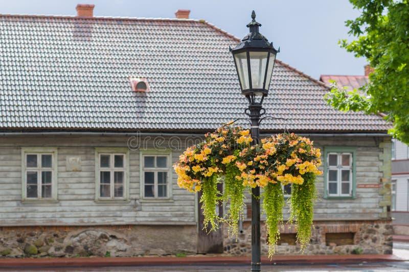Lâmpada de rua do vintage com os potenciômetros de flor de suspensão no dia chuvoso imagens de stock