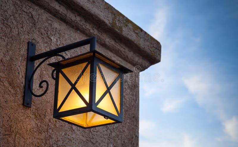 A lâmpada de rua montou na parede de pedra sobre o céu azul foto de stock royalty free