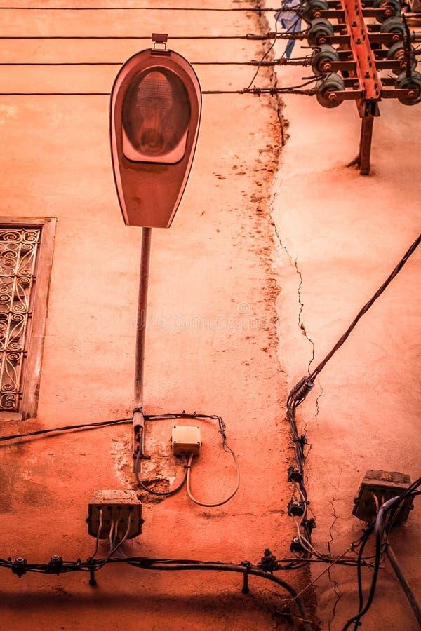 Lâmpada de rua na parede suja com linhas de abastecimento do poder foto de stock