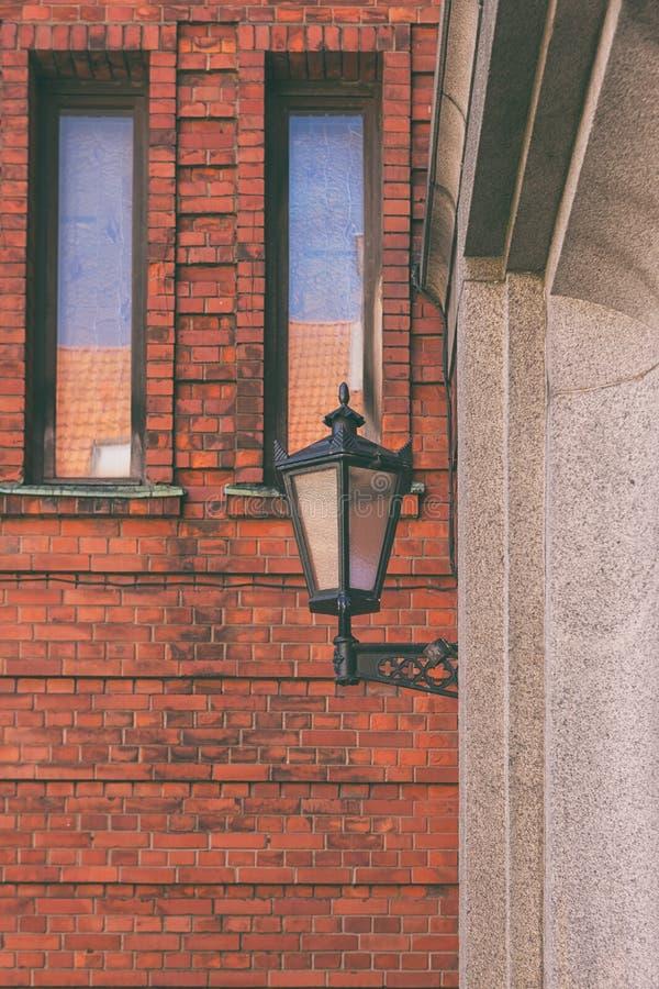 Lâmpada de rua na parede vermelha imagem de stock
