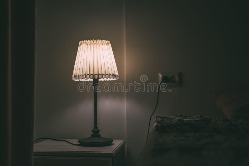 Lâmpada do quarto na tabela de noite na sala de hotel na noite fotografia de stock