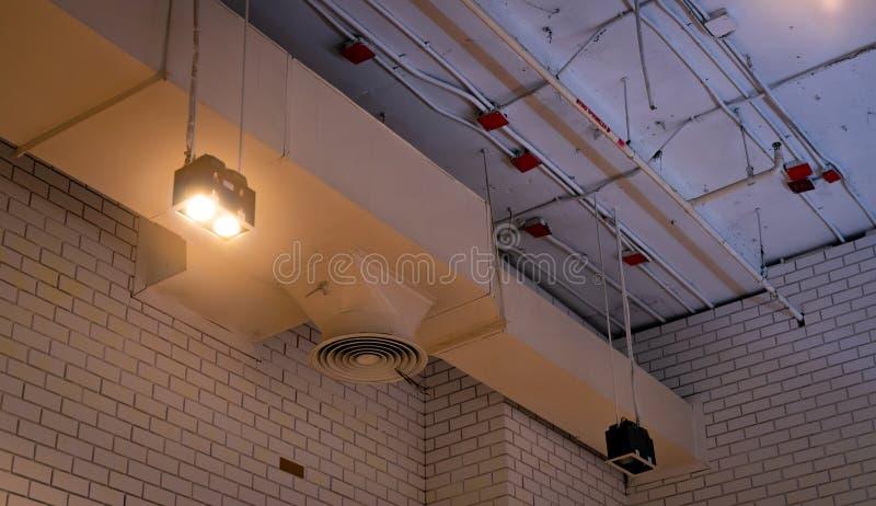 Lâmpada do teto com o canal aberto da luz e de ar que pendura no teto Sistema de tubulação do condicionador de ar Sistema de vent imagens de stock