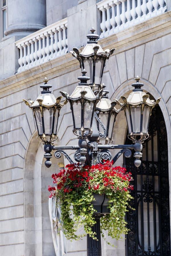 A lâmpada do vintage do metal da rua com suspensão do gerânio vermelho floresce foto de stock