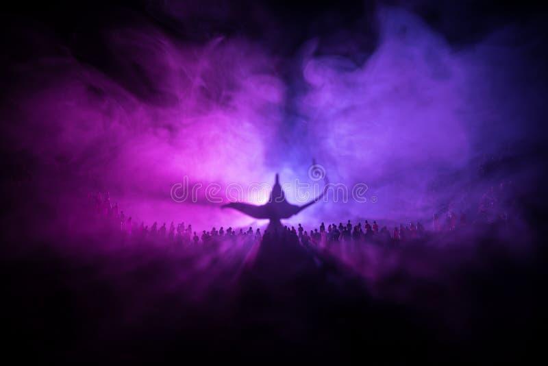 Lâmpada dos desejos Silhueta de uma grande multidão de povos que estão contra uma lâmpada grande dos desejos com feixes luminosos fotografia de stock