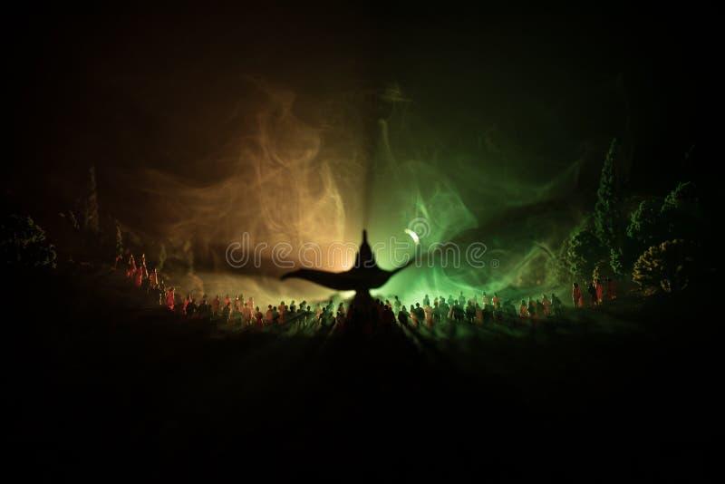 Lâmpada dos desejos Silhueta de uma grande multidão de povos que estão contra uma lâmpada grande dos desejos com feixes luminosos imagem de stock royalty free