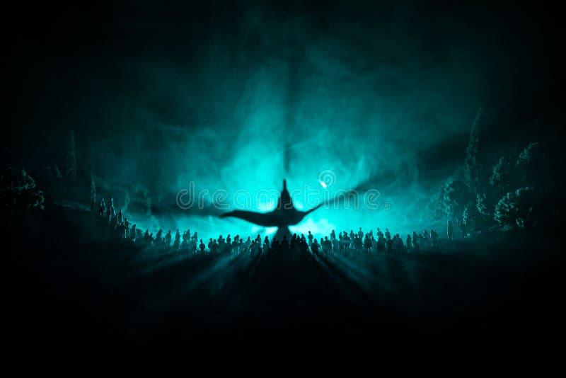 Lâmpada dos desejos Silhueta de uma grande multidão de povos que estão contra uma lâmpada grande dos desejos com feixes luminosos foto de stock