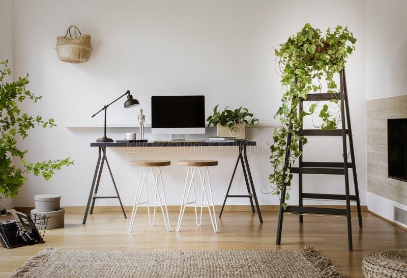 Lâmpada e computador de secretária na mesa preta em wi interiores do espaço de trabalho fotos de stock