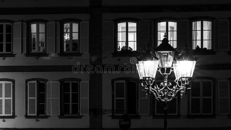 Lâmpada e construções de rua com janelas destacadas, opinião da noite de Strasbourg foto de stock