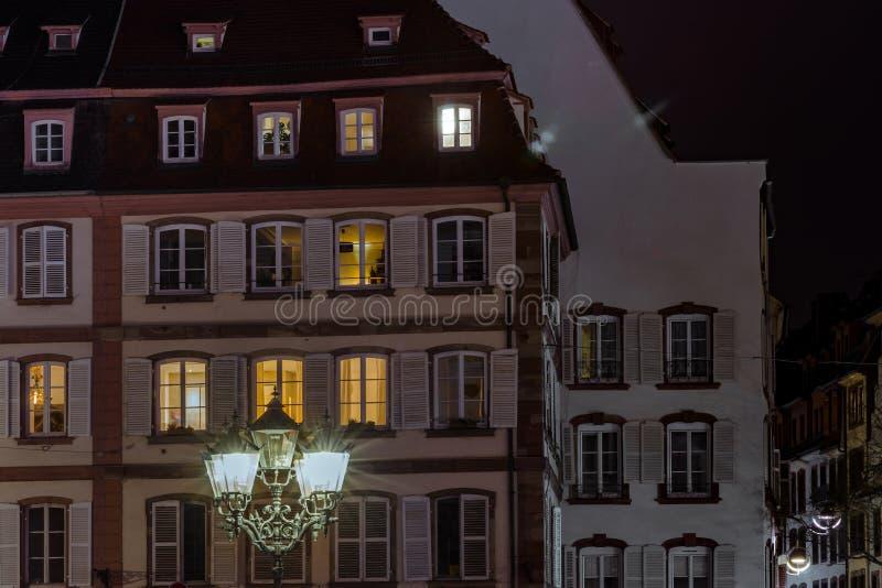 Lâmpada e construções de rua com janelas destacadas, opinião da noite de Strasbourg foto de stock royalty free