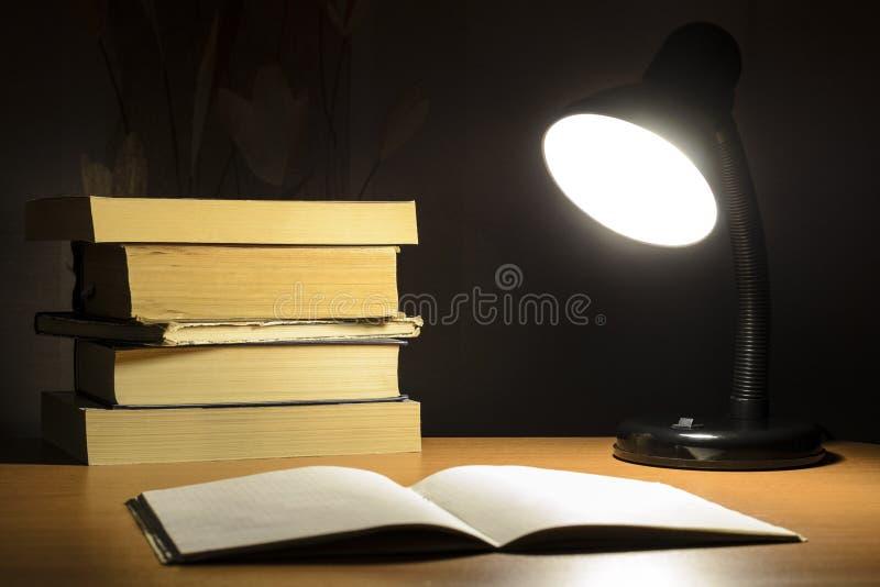 Lâmpada e livros na obscuridade foto de stock