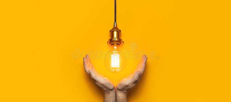 Lâmpada edison elegante em mãos masculinas de fundo amarelo brilhante Espaço de cópia de texto plano de exibição superior conceit imagem de stock royalty free