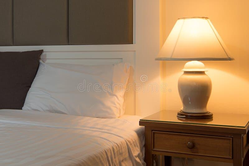 Lâmpada em uma tabela de noite ao lado da cama clássica imagem de stock royalty free