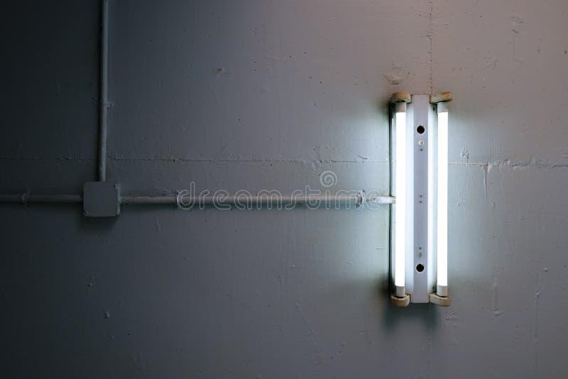 Lâmpada fluorescente longa instalada no teto concreto na fábrica industrial imagem de stock royalty free