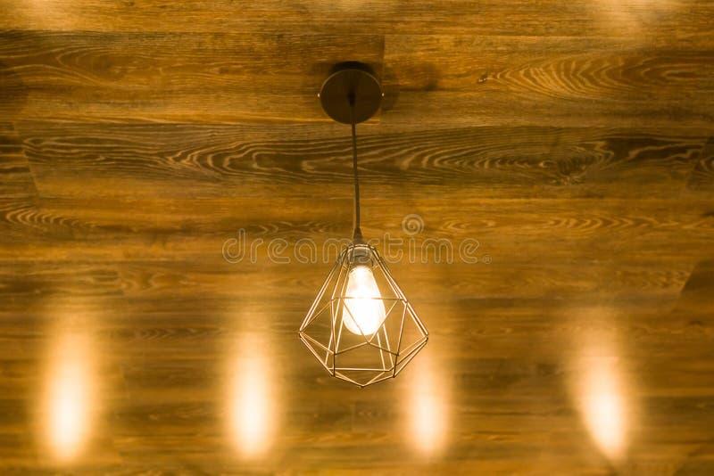 Lâmpada geométrica à moda moderna em um teto de madeira marrom de bronze foto de stock royalty free