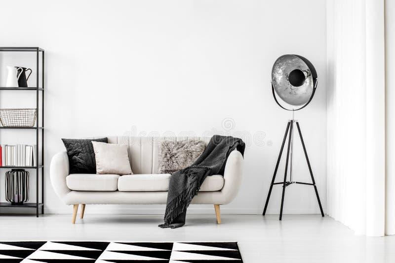 Lâmpada industrial ao lado do sofá bege com cobertor e travesseiros, espaço de cópia na parede branca vazia foto de stock