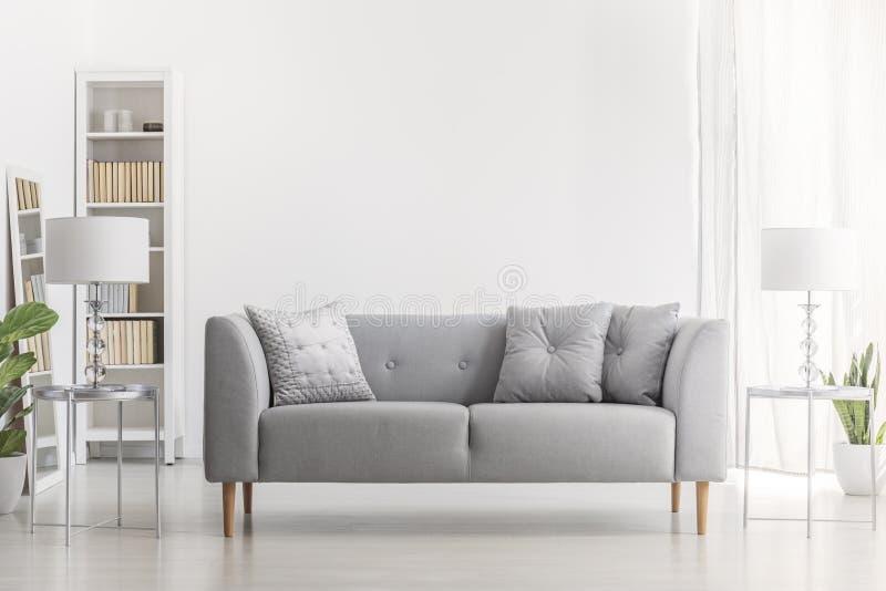Lâmpada na tabela de prata ao lado do sofá cinzento com os descansos na sala de visitas branca interior com planta Foto real foto de stock royalty free