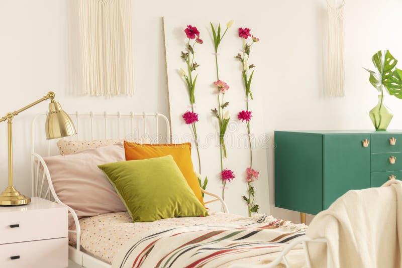 Lâmpada no nightstand cor-de-rosa pastel ao lado da única cama do metal com os descansos cor-de-rosa do verde azeitona, os alaran fotos de stock