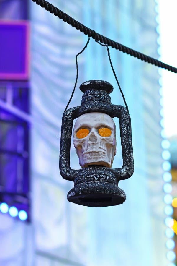 Lâmpada que contém um crânio iluminado na frente de um trem de fantasma fotografia de stock