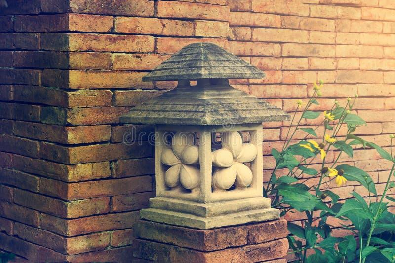 Lâmpada que japonesa da lanterna da pedra do jardim em torno das flores cresce foto de stock