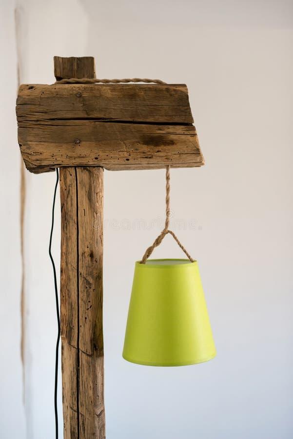 Lâmpada rústica do vintage feita de feixes de madeira e da base velhos do coto contra o interior branco em uma casa da vila fotos de stock