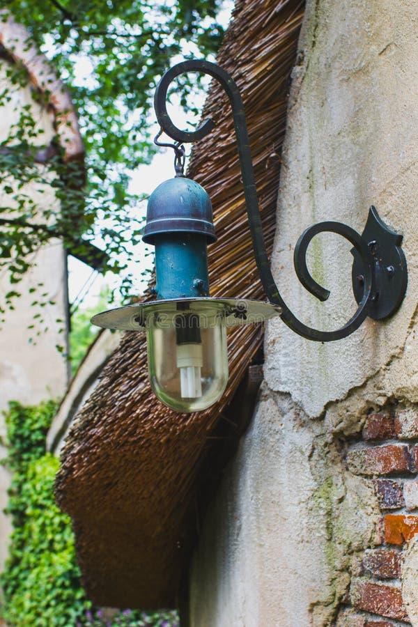 Lâmpada velha, lanterna, na parede de tijolo da casa fora do close-up imagem de stock