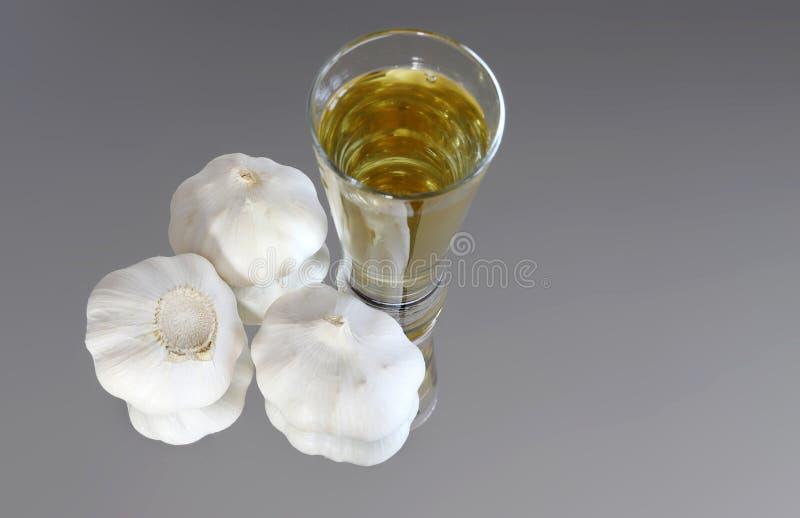 Lâmpadas de alho e cascas de alho num espelho com um copo de álcool raquia imagens de stock royalty free