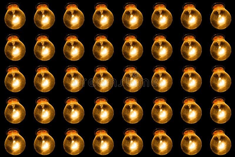 Lâmpadas de incandescência em um fundo preto Muitas lâmpadas brilham em seguido com luz amarela Conceito do sótão fotografia de stock
