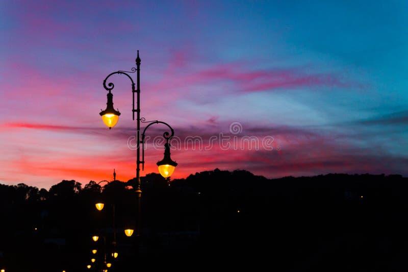 Lâmpadas de rua com o céu bonito e colorido do por do sol fotografia de stock