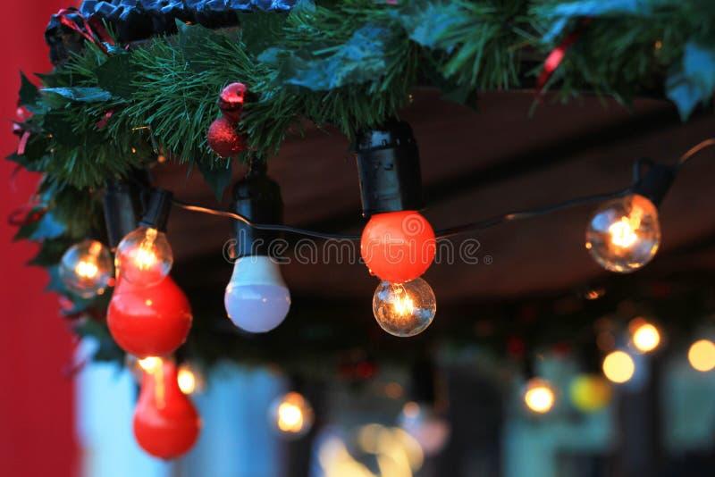 Lâmpadas de uma festão na árvore de abeto verde Fundo abstrato da decoração do Natal imagem de stock royalty free