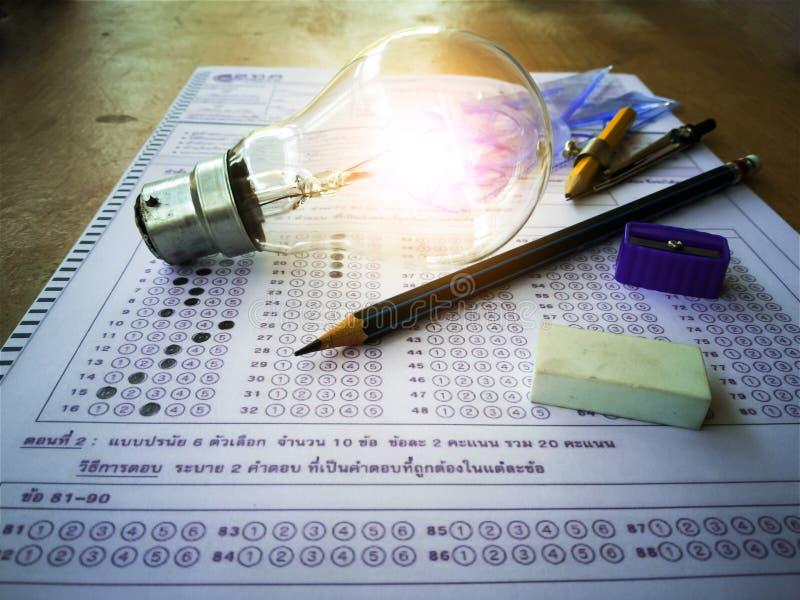 Lâmpadas e artigos de papelaria colocados na folha de resposta com conceitos educacionais imagem de stock royalty free
