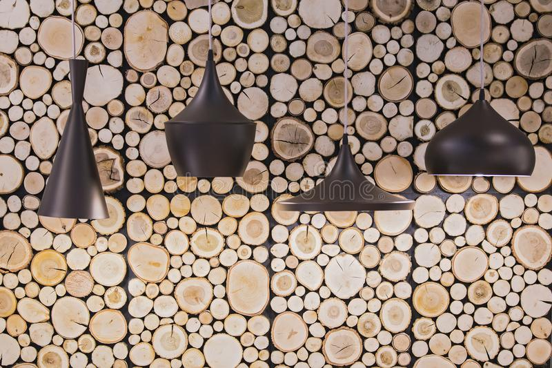 Lâmpadas pretas em um café que pendura em um fundo de cabanas rústicas de madeira de madeira na parede imagem de stock