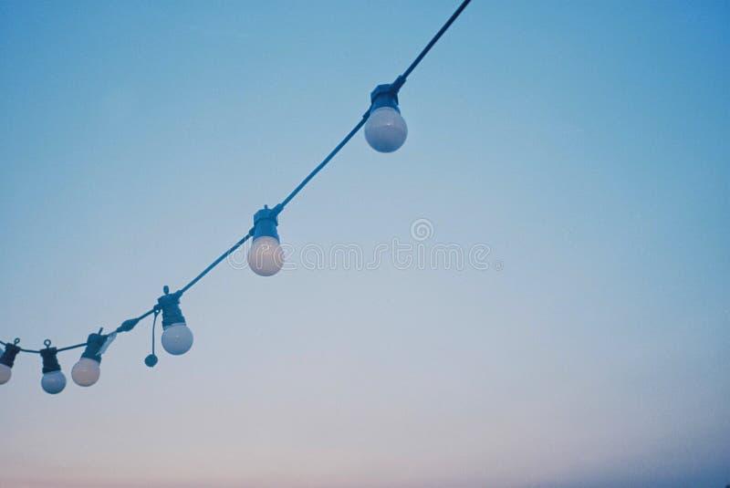 Lâmpadas que penduram em uma corda com o céu branco claro bonito imagens de stock royalty free